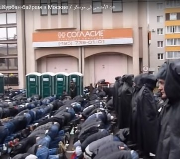 A collective prayer during the Kurban Bayramı Muslim festival in Moscow. Due to the dire shortage of mosques in the city, the faithful pray under the rain in the street while Russian policemen in black rain coats watch over them. (Image: video capture)