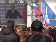 Participants of a rally in occupied Sevastopol watch Russian President Vladimir Putin from a screen.