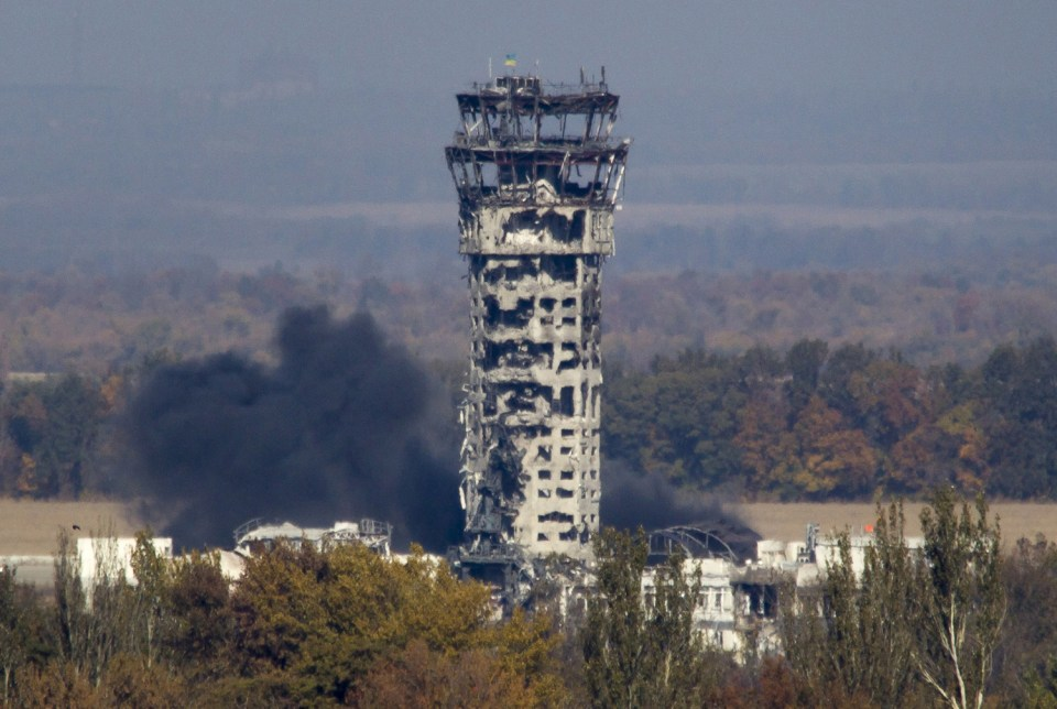 A Ukrainian national flag flies at top of a badly damaged traffic control tower as smoke rises after shelling at the airport on October 12, 2014.