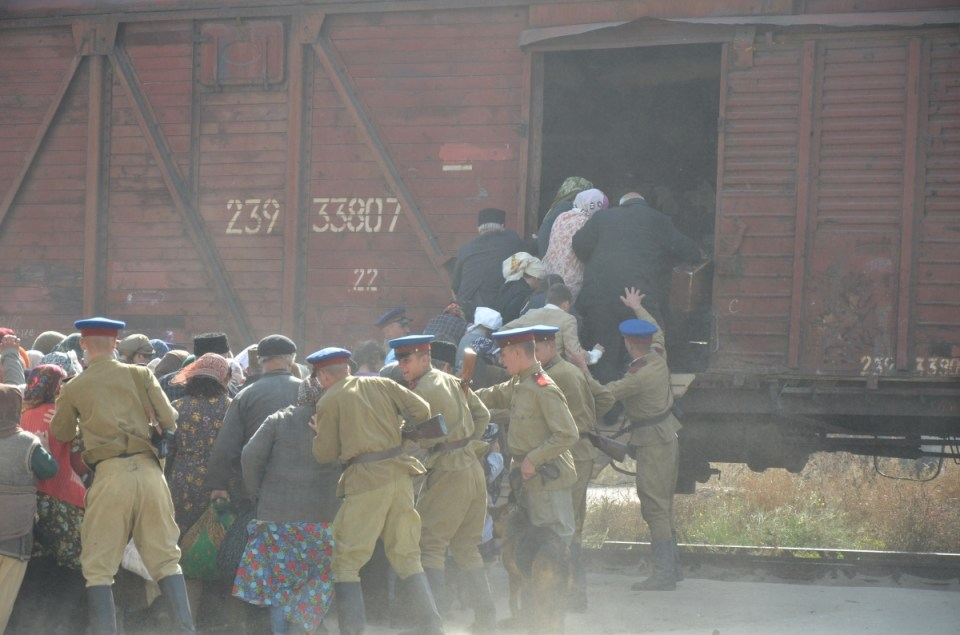 NKVD soldiers drive Crimean Tatar women, children, and elderly to the cattle wagons. Snapshot from the film