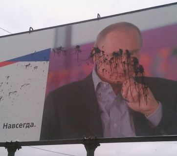 A billboard with Russian President Vladimir Putin installed in the Crimean city of Kerch aftern the annexation was sprayed with black paint. September 2015 (Image: public domain)