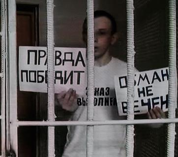 "Ruslan Zeytullaev, political hostage of the Kremlin, with the posters ""Lies won't last forever"" and ""Truth will prevail,"" 27 July 2017. Photo: Anton Naumlyuk"