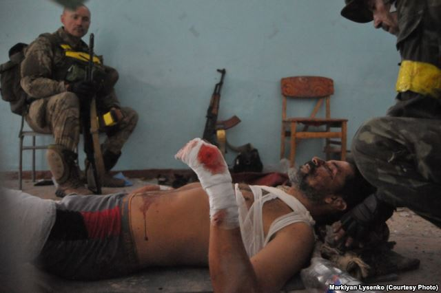 Ukrainian soldiers are bandaging their wounded commander Photo: Markiyan Lysenko