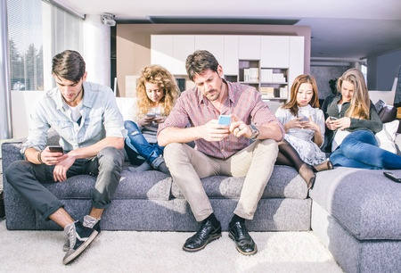52142855 - young people looking down at cellular phone. sitting on the couch and ignoring each others to focus on the smart phones.