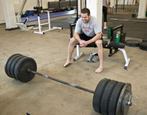 Man looking at loaded barbell