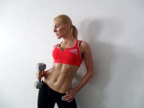 Woman with six pack holding a dumbbell