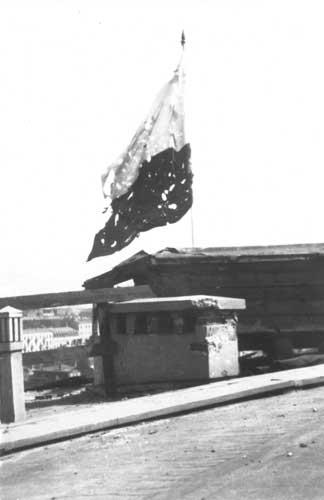 Przestrzelona flaga polska nad powstańczą Warszawą