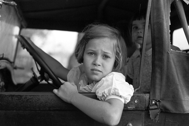 Child of farmer sitting in automobile waiting for father to come out of general store