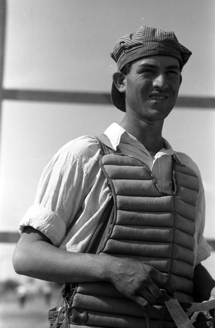 Migratory laborer in a catchers uniform at the Agua Fria Migratory Labor Camp, Arizona; photograph by Russell Lee
