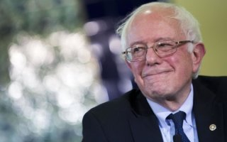 """Senator Bernie Sanders, an independent from Vermont and 2016 Democratic presidential candidate, smiles during an interfaith roundtable in Washington, D.C., U.S., on Wednesday, Dec. 16, 2015. Sanders said figures like Trump attempt to """"divide"""" Americans. """"A few months ago we're supposed to hate Mexicans and he thinks they're all criminals and rapists and now we're supposed to hate Muslims, and that kind of crap is not going to work in the United States of America,"""" he said. Photographer: Drew Angerer/Bloomberg via Getty Images"""