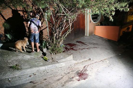 Morador observa sangue de vítimas no local dos assassinatos, em Carapicuíba (Grande SP)