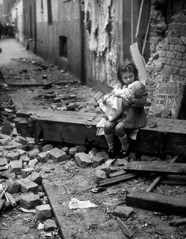 Liten jente sitter utenfor sitt hus i London, 1940