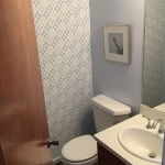 The $400 bathroom remodel. A little wallpaper, refinisheddoor and  cabinet, and a new doorknob.