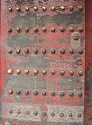 An old door with rivets and a lot of the red paint worn off.