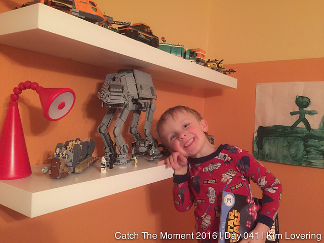 Henry in front of a LEGO shelf