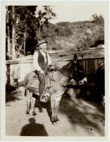 Wilbur M. Sturtevant on a burro at his stables