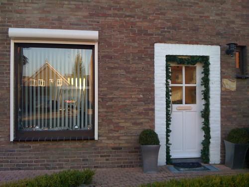 Voordeur en vensterbank voorzien van guirlande met lampjes...