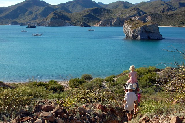 Kids hike to sailboats in the bay at San Juanico