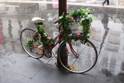 Fake flowers tied around a parked bike advertising a clothes shop on Bourke Street