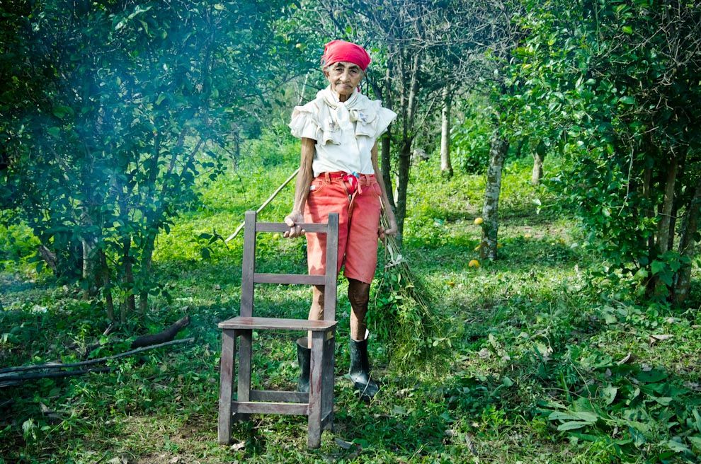 Una anciana barre la superficie donde su familia se asentará temporalmente debido a las inundaciones de las aguas del Río Jejuí, en Puerto La Niña, departamento de San Pedro. (Elton Núñez)