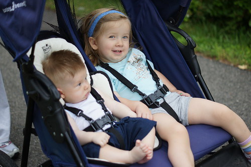 My kids, holding hands in the stroller.
