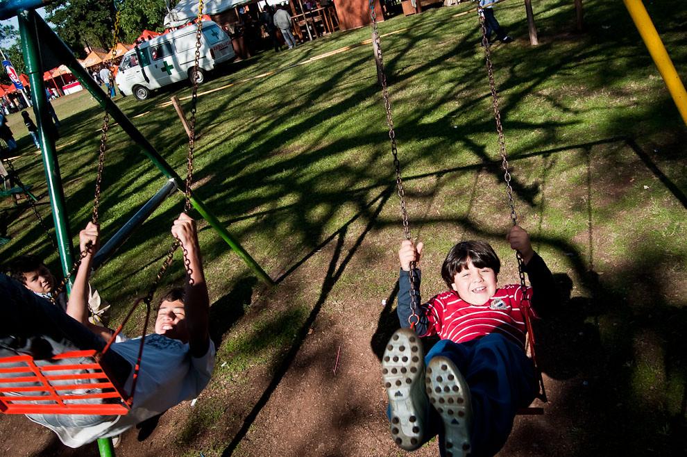 Niños se divierten en el parque de juegos de la Plaza San Miguel, mientras se preparan los escenarios y stands para lo que será el festival más importante de la cuidad. (Elton Núñez, San Miguel - Paraguay)