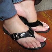 Nackte Frauenfüße in schwarzen Sanadalen