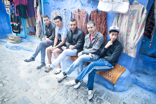 Bryanboy with a group of Moroccan boys crossing their legs at Chefchaouen Medina, Morocco