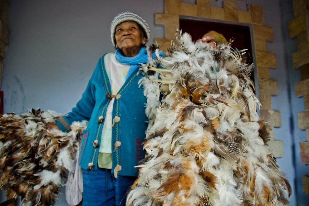 Ña Andresa, una promesera de 77 años, nos muestra su traje hecho de plumas de aves, que cada año utiliza para representar la cultura de los Guaicurúes en la época de celebraciones de la fiesta al Patrono San Francisco Solano, en Emboscada, departamento de Cordillera. (Elton Núñez)