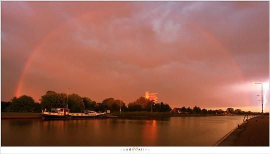 De regenboog tegen een met onweer gevulde lucht, met rechts nog net een bliksemschicht.