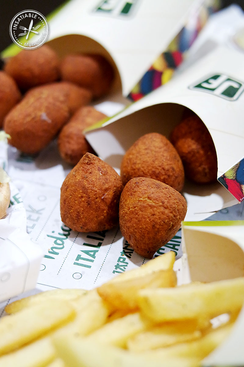 Golden brown spinach and cheese filled falafel poppers spill out of their cardboard obtainer onto a tray.