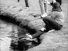 "Still frame from CBC Vancouver's ""The Be-In"" (1967), woman dipping her feet in the pond."