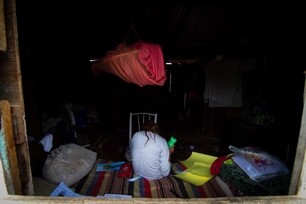 Una niña realiza sus tareas escolares en el interior de su precaria vivienda mientras los voluntarios construyen su nueva vivienda en el patio trasero. (Tetsu Espósito - Lambaré, Paraguay)