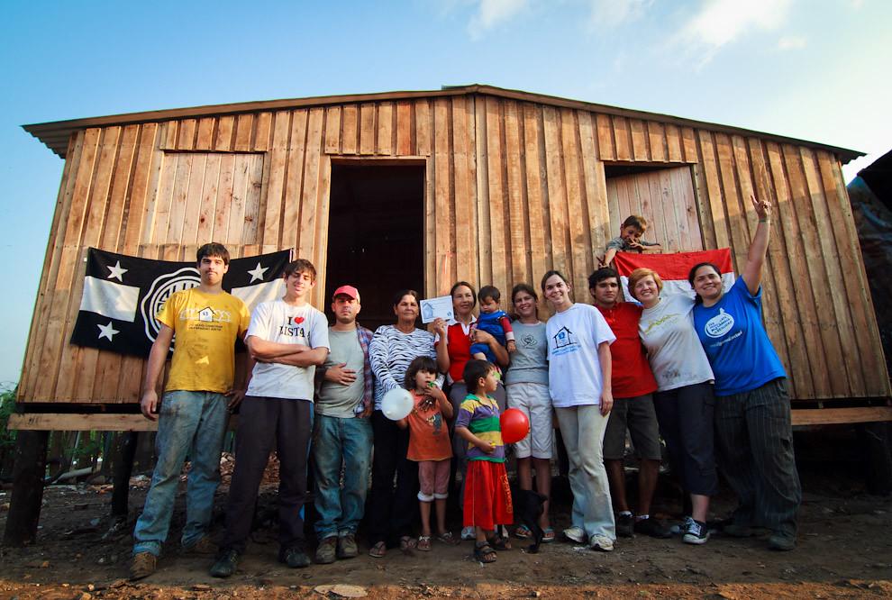 Fotografías de trabajo y solidaridad obtenidas en los 3 días de construcción de casas de emergencia con la Organización Un Techo Para mi País. Jóvenes de la Cuadrilla posan con Doña Ignacia con su vivienda finalizada en el barrio de Yukyty - Bañado Sur (Tetsu Espósito - Lambaré, Paraguay)