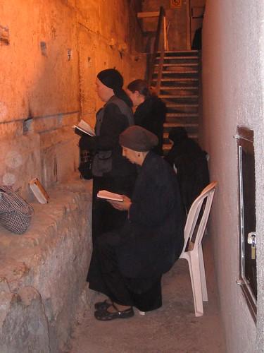 Women pray opposite the longest stone