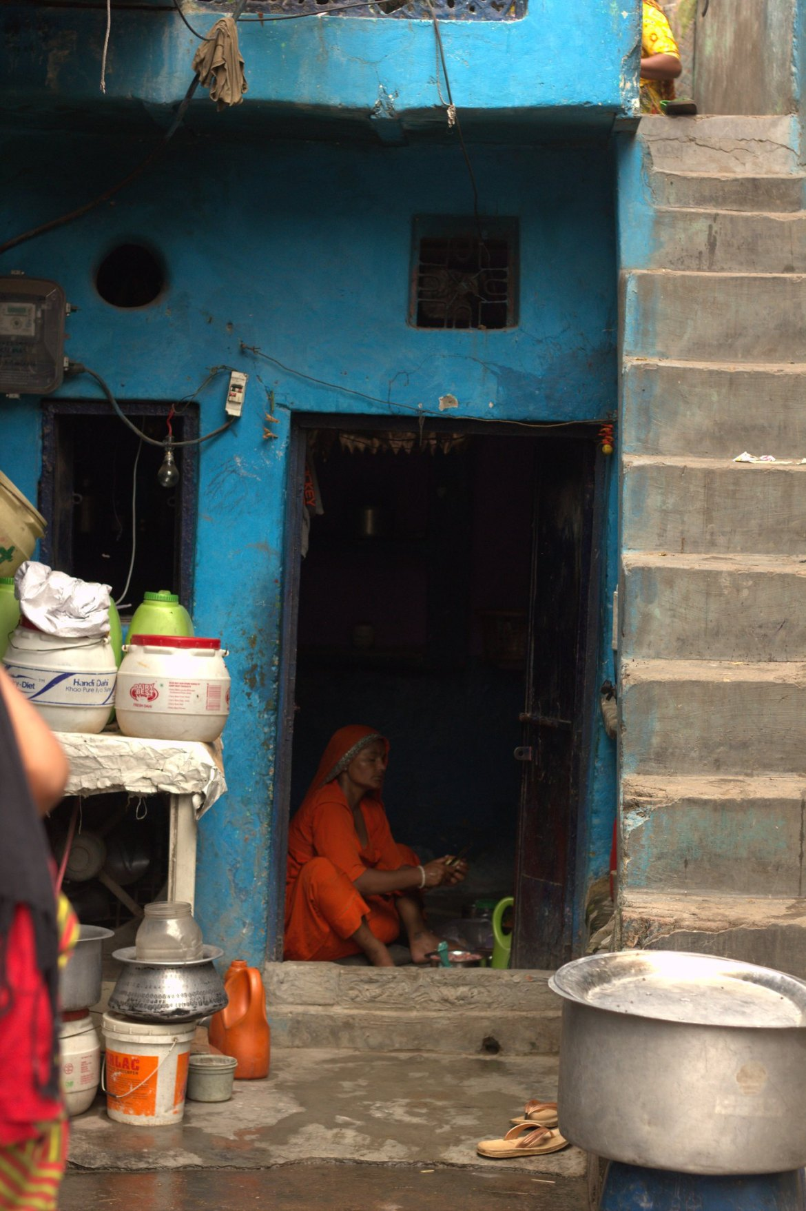 A woman cooks in a flimsy hut in Kathputli Colony