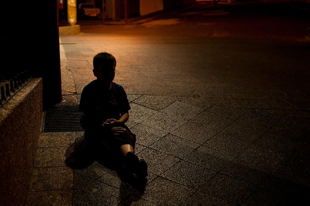 Un niño de la calle esta sentado en el piso mientras espera la hora de volver a su casa al caer la noche, luego de una larga jornada pidiendo limosnas sobre la Avenida Sacramento. (Elton Núñez - Asunción, Paraguay)