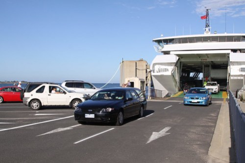 Cars drive off the ferry at Queenscliff, cars to the left waiting to drive on