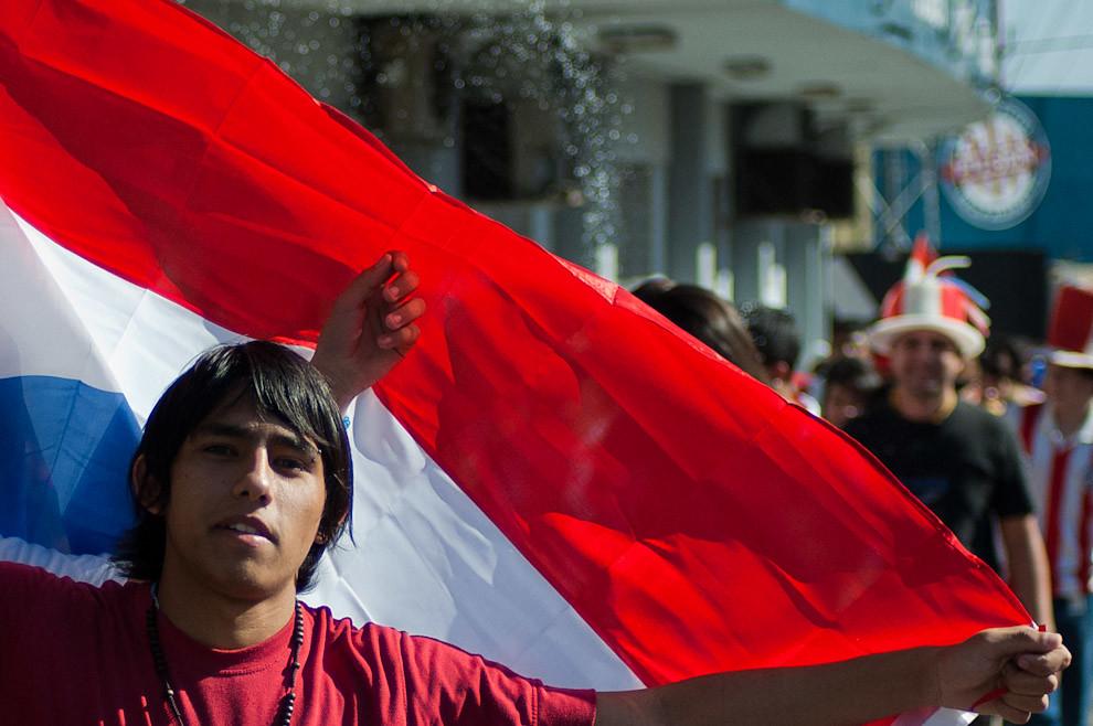 Un muchacho levanta su bandera Paraguaya en la fila de acceso a Platea durante la espera por el partido Paraguay-España en los Cuartos de finales del Mundial de Futbol Sudáfrica 2010. (Elton Núñez - Asunción, Paraguay)