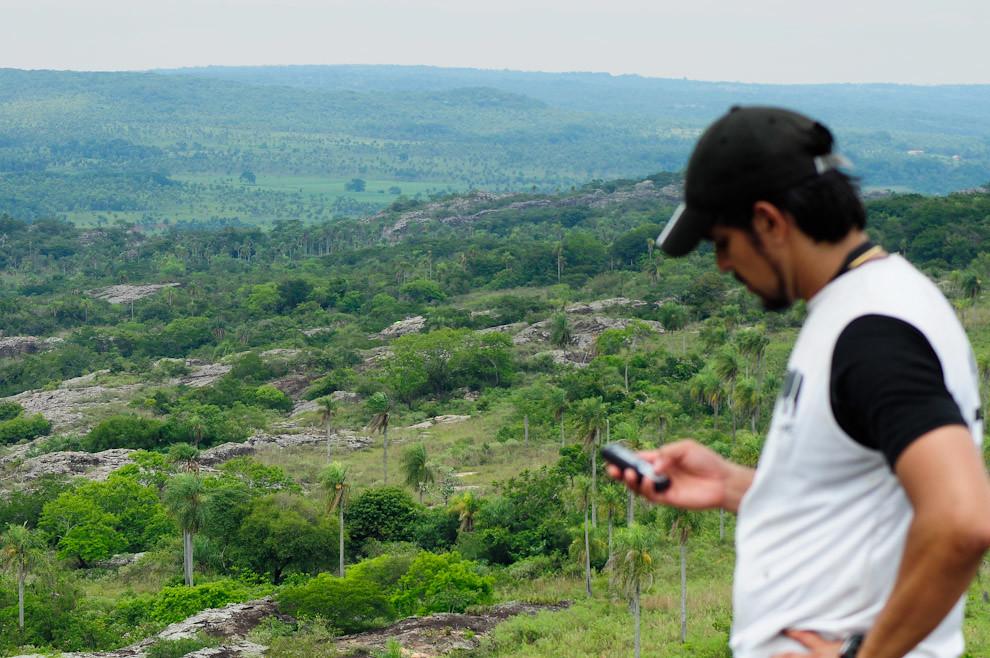 Marcelo Florentín, coordinador y jefe de móviles, inspecciona el Puesto de Control 04 y realiza llamadas a los otros puestos desde la cima del Cerro Naranjo. (Elton Núñez - Piribebuy, Paraguay)