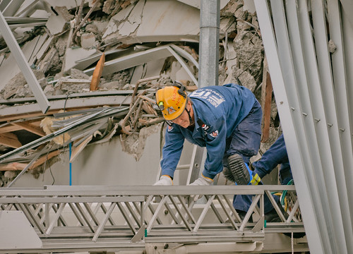 Rescue worker climbs out of rubble