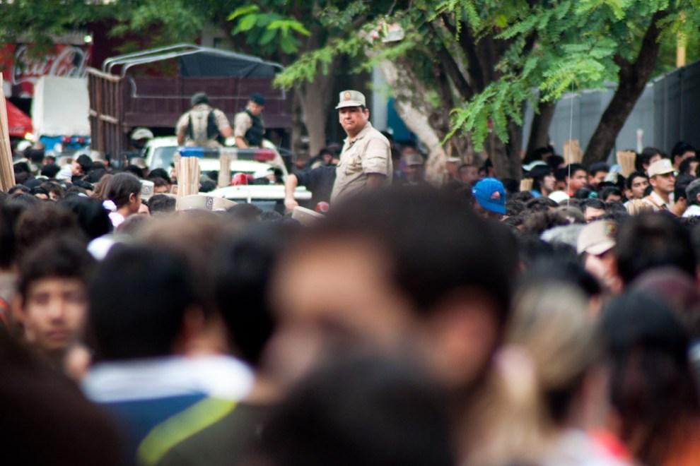 Un Policía se para sobre una patrulla para vigilar el orden en la multitud que se congregó en las calles cercanas a la Basílica en la mañana en que se celebraba la Misa Central. Mucha gente apretujada no podía avanzar ni retroceder, la única opción era conservar el lugar en donde se estaba y participar de la Misa hasta que acabara. (Elton Núñez - Caacupé, Paraguay)