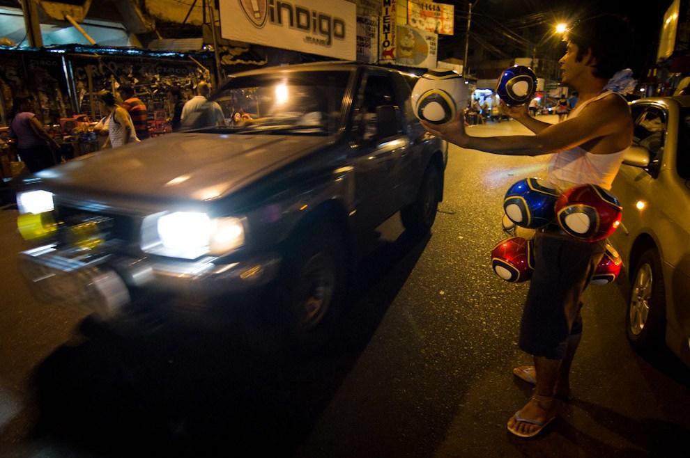 Un vendedor ambulante ofrecía distintas pelotas a los andantes sobre la Avenida Petirossi la madrugada de la víspera del día de los Reyes Magos. (Tetsu Espósito - Asunción, Paraguay)