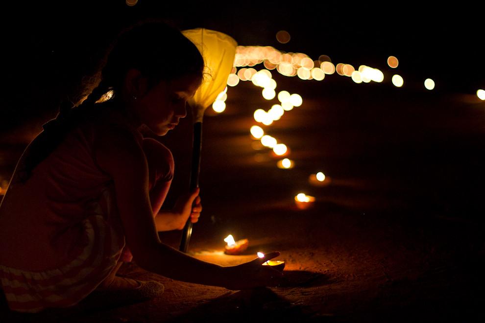 Una niña al borde del camino, iluminado por miles de velas que guían a los feligreses que acompañan a la Virgen. (Tetsu Espósito - San Ignacio, Paraguay)