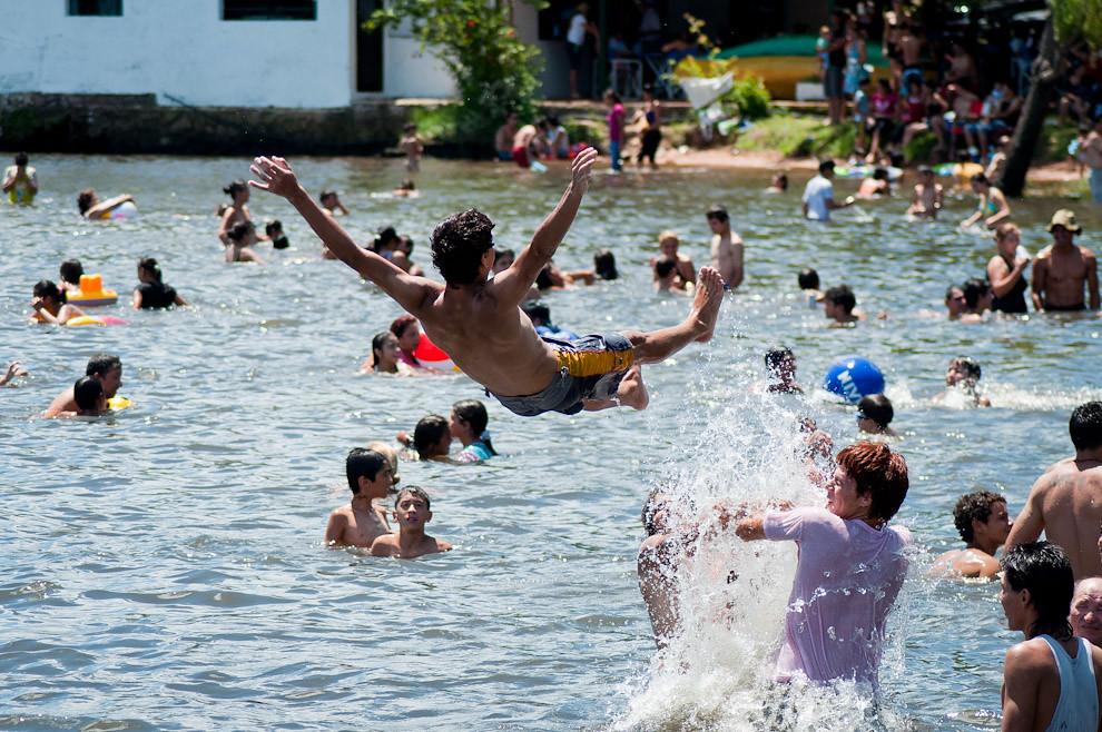 Unos muchachos se divierten arrojando a su amigo al agua en una de las costas del Lago Ypacaraí el domingo 23 de Enero pasado. (Elton Núñez - Ypacaraí, Paraguay)