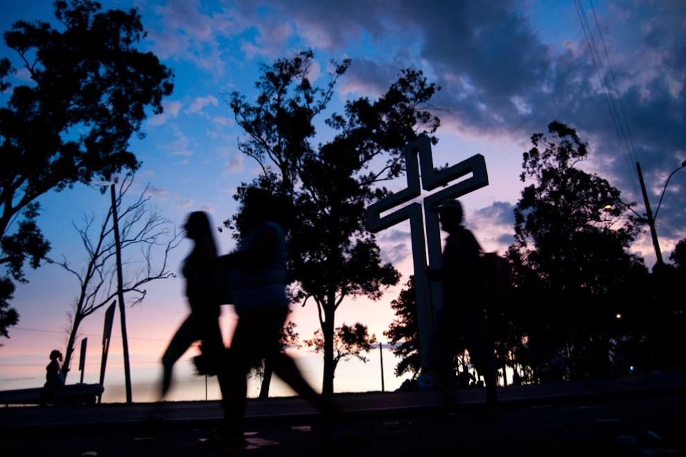"""Peregrinos caminan hacia la Ciudad de Caacupé frente al monumento llamado """"Curuzú Peregrino"""" después de la caída del Sol el 7 de Diciembre. (Elton Núñez - Caacupé, Paraguay)"""