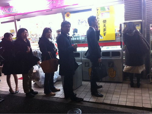 Line of people waiting to use a public telephone in Tokyo