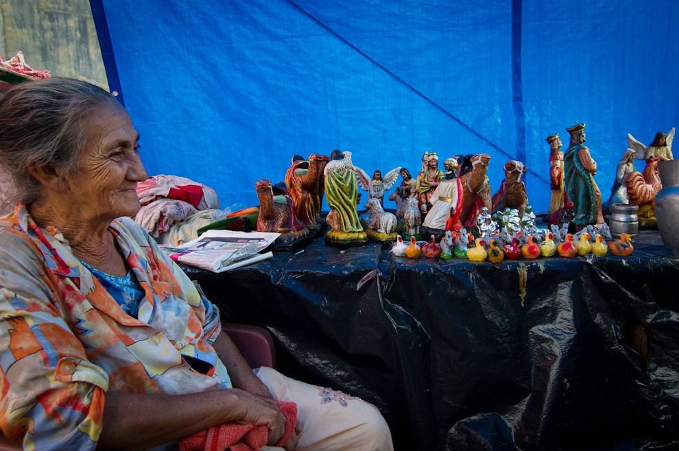 En el Mercado 4, bajo  la sombra y para refugiarse del acuciante calor, una anciana atiende su negocio de venta de pesebres. (Tetsu Espósito -  Asunción, Paraguay)