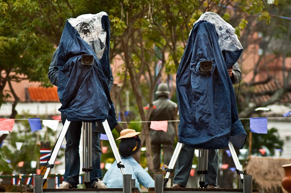 Dos camarógrafos se refugian de la fría llovizna mientras trabajan en la cobertura de los espectáculos artísticos durante la Fiesta de San Juan que duró toda la jornada del 25 de Junio en las cuatro plazas del Cabildo en Asunción. (Elton Núñez)