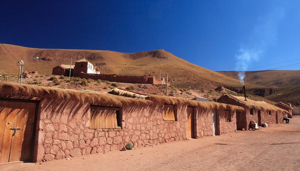 Los escasos habitantes de estas 10 casas de piedra, adobe y paja, se dedican al pastoreo; fines de semana asisten a la capilla que ven en lo alto. Machuca, pequeño pueblo ancestral en el altiplano chileno (Guillermo Morales)